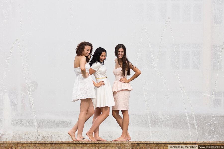 Три босоногие девушки фотографирутся у фонтана