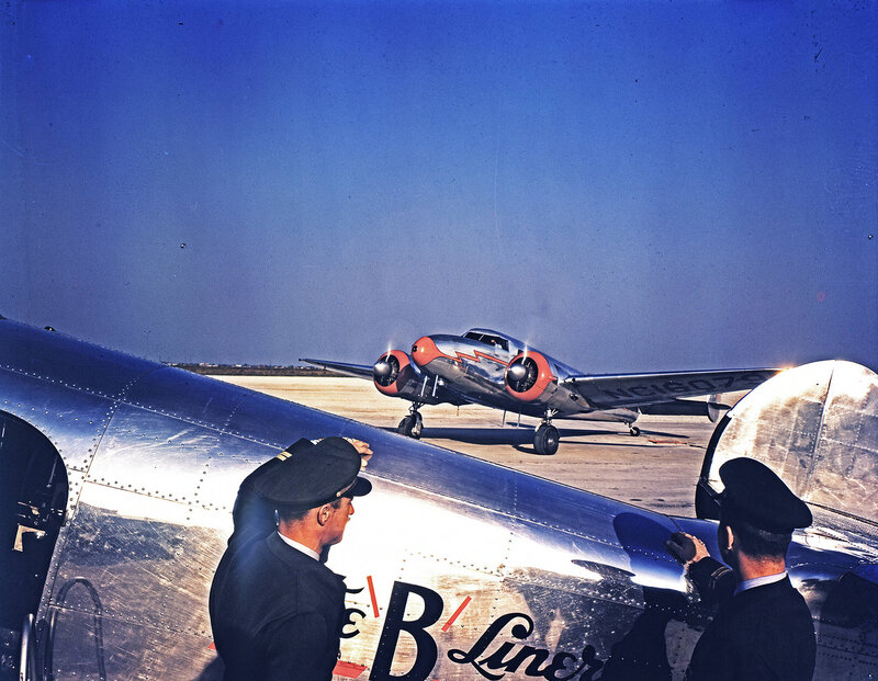 Two Braniff Airline pilots, standing behind a Lockheed Model 10B Electra, watching a Lockheed Model 12A Electra Junior, belonging to the Continental Oil Company, maneuver on the tarmac at William P. Hobby Airport in Houston, Texas. March 1940