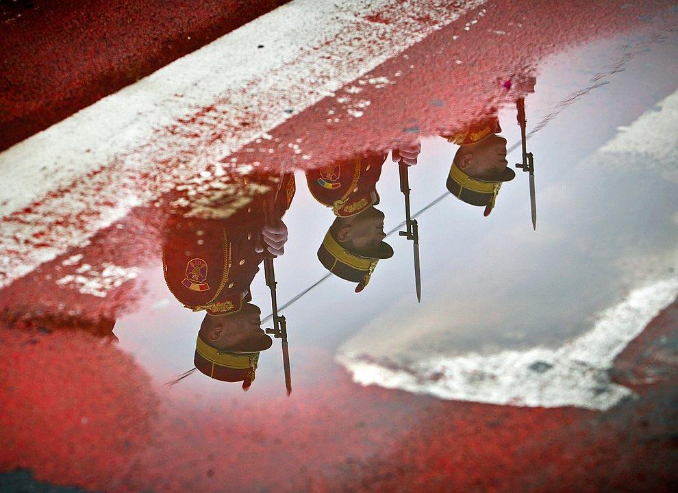 Отражение в дорожном зеркале.  Работник устанавливает большой плакат, Ливан, 15 февр