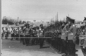 Император Николай II и командир полка генерал-майор Николай Михайлович Киселевский (слева от Николая II) обходят строй солдат.