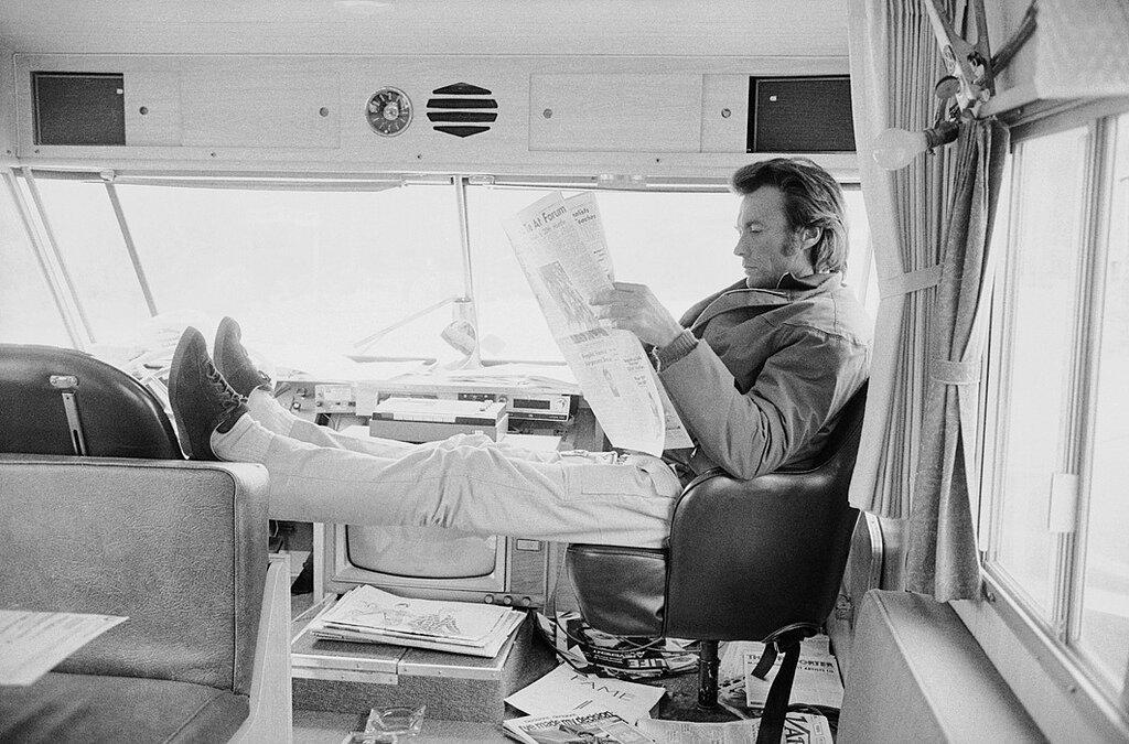 Клинт Иствуд за чтением газеты в трейлере в перерыве между съемками