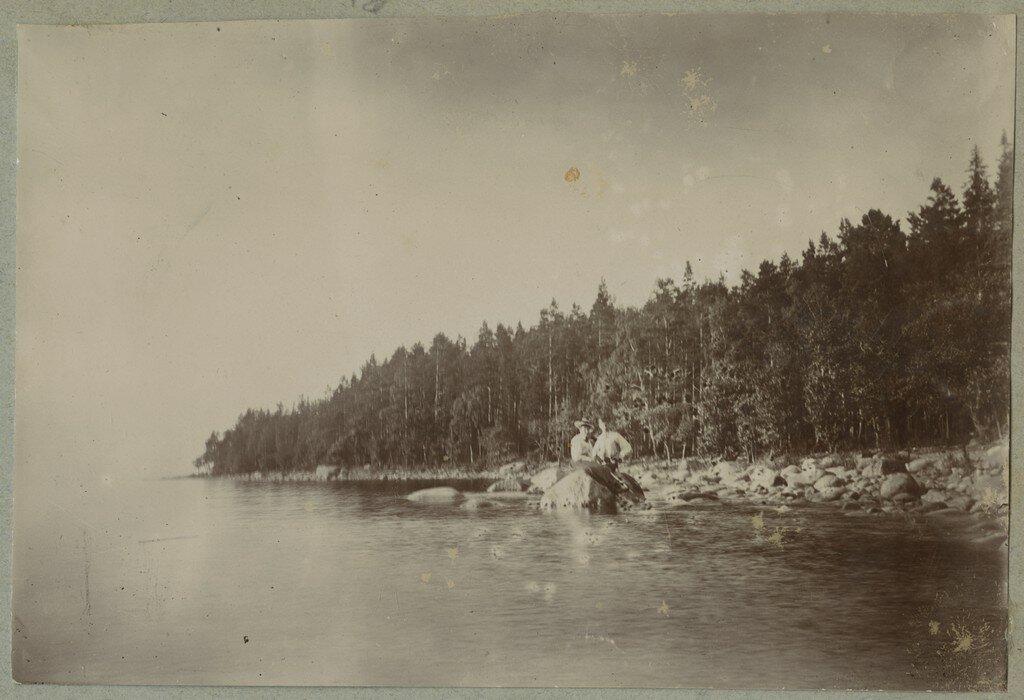 1900. Женщина и мужчина сидят на валуне