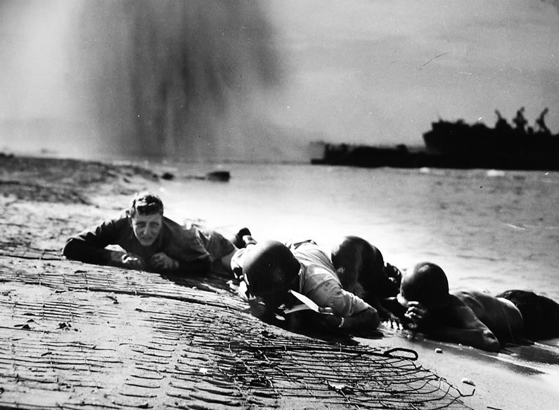 American Coast Guardsmen and Naval personnel take cover as a bomb dropped by a German plane explodes behind them during the landings at Salerno, 1943