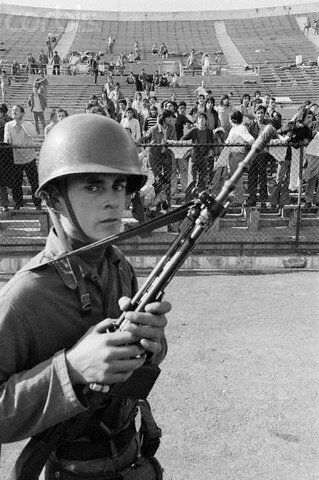 Armed Guard with Prisoners in Stadium
