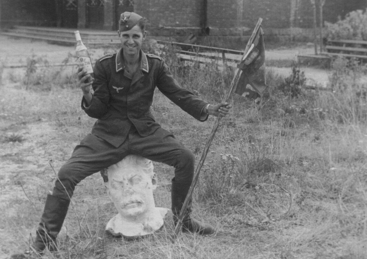 Без даты. Унтер-офицер люфтваффе позирует с бутылкой сидя на голове бюста И.В. Сталина