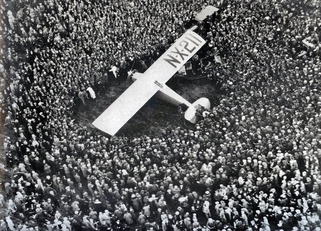 Lindberg's Spirit of St Louis surrounded by thousands of spectators after landing in Paris. May 21, 1927