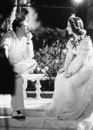 7th April 1936:  Director George Cukor chatting to Norma Shearer on the set of the lavish MGM production of Shakespeare's 'Romeo and Juliet'. Norma Shearer earned an Academy Award for her performance as Juliet.  (Photo by William Grimes/John Kobal Foundat