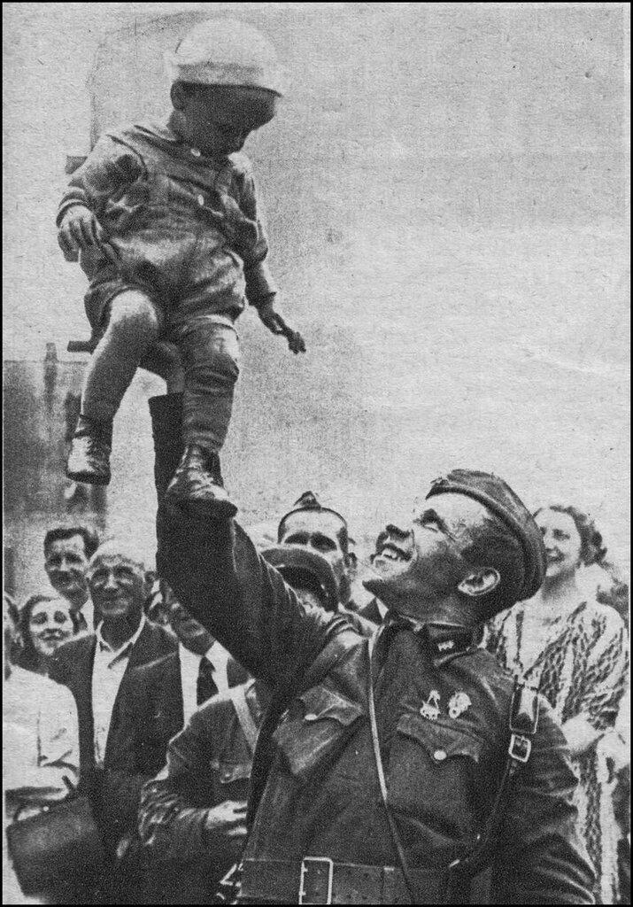 Командир РККА поднимает на руке латышского мальчика. Снимок сделан вскоре после ввода Красной армии на территорию Латвии.