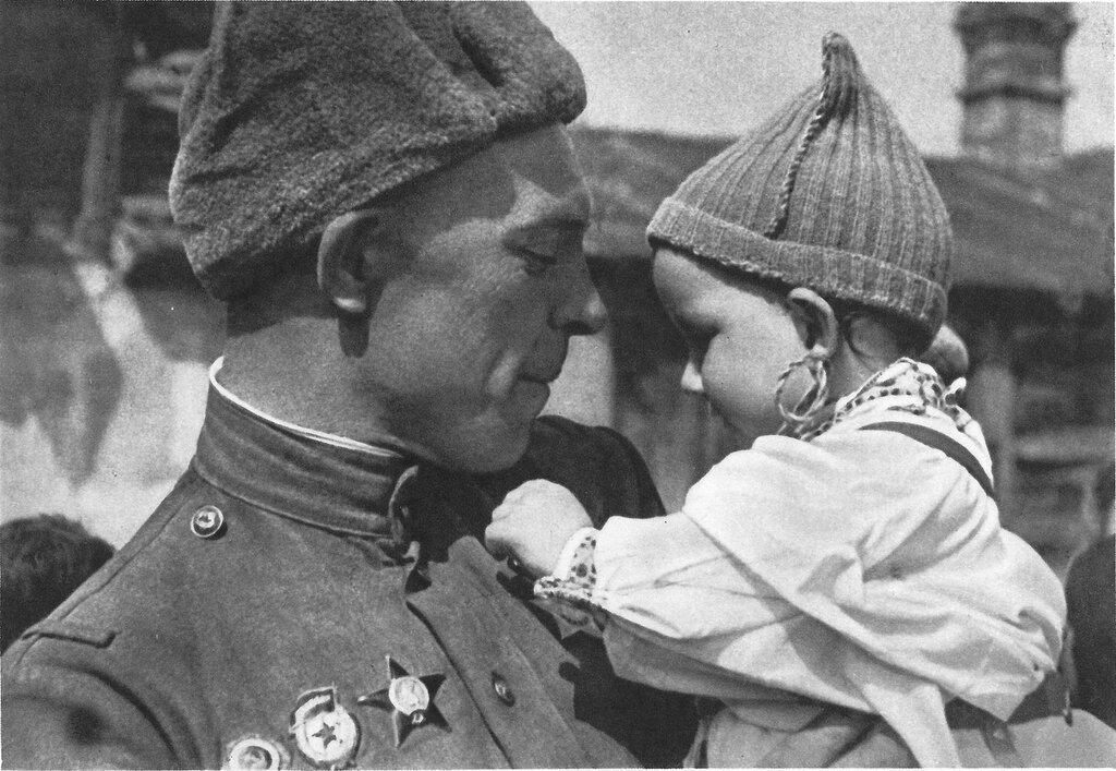 Советский солдат с чешским ребенком на руках. Малыш рассматривает орден Славы на груди бойца.Прага, Чехословакия. Май 1945