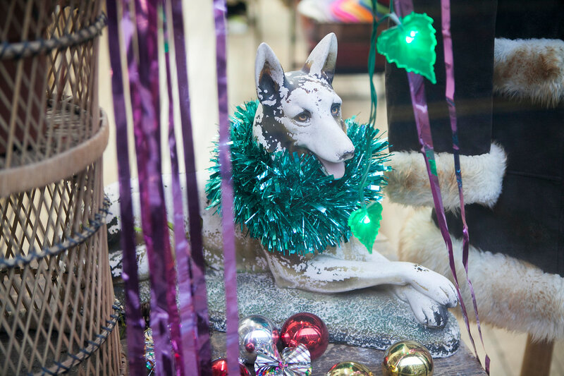 a dog sculpture decorated with tinsel in a shop window