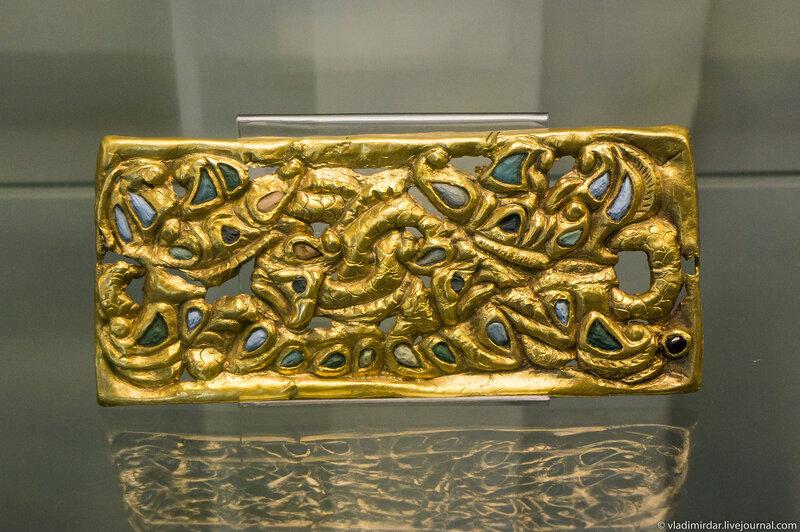 Золотая поясная пластина. Изображена сцена борьбы драконов с грифонами.