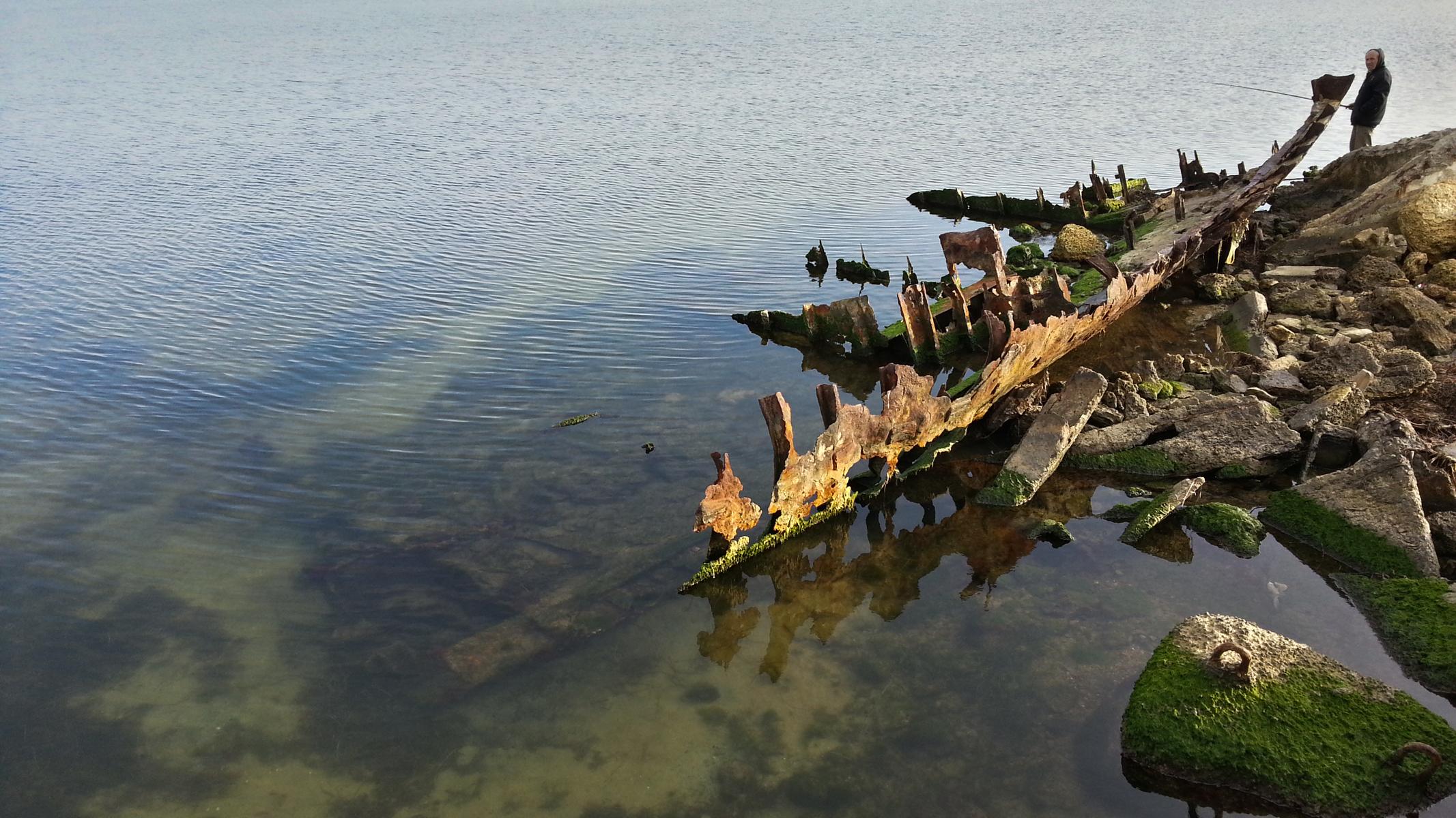 Рыбак удит рыбу рядом с остовом какого-то судна.