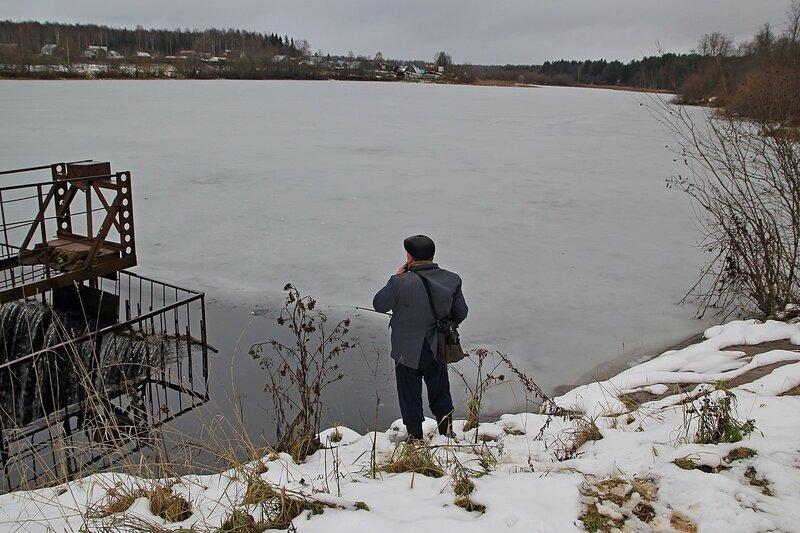 Рыбак у водосброса покрытого льдом пруда на реке Плоской в Коминтерне