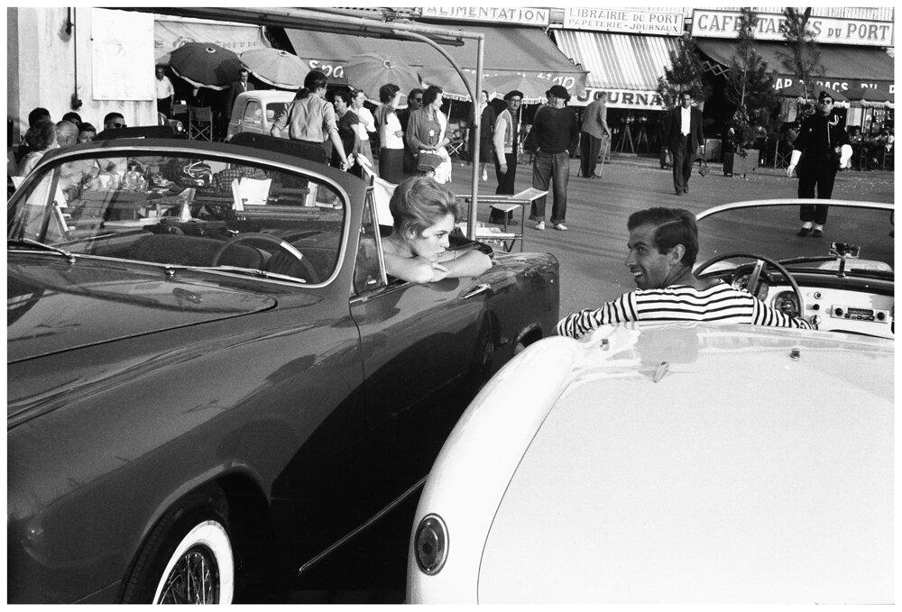 Brigitte BARDOT dans son cabriolet Simca Week-end et Roger VADIM dans son spider Lancia Aurelia B24 se croisant sur le vieux port de SAINT-TROPEZ, à l'époque du tournage du film