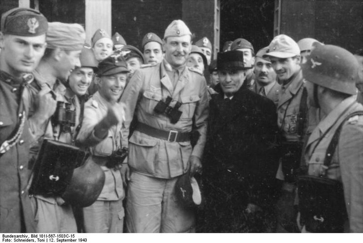 B. Mussolini with his SS rescuer, Otto Skortzeny (tall man to his right) outside the hotel on top of Gran Sasso from where the Italian dictator was snatched on Hitler's personal orders, Sept 12, 1943.