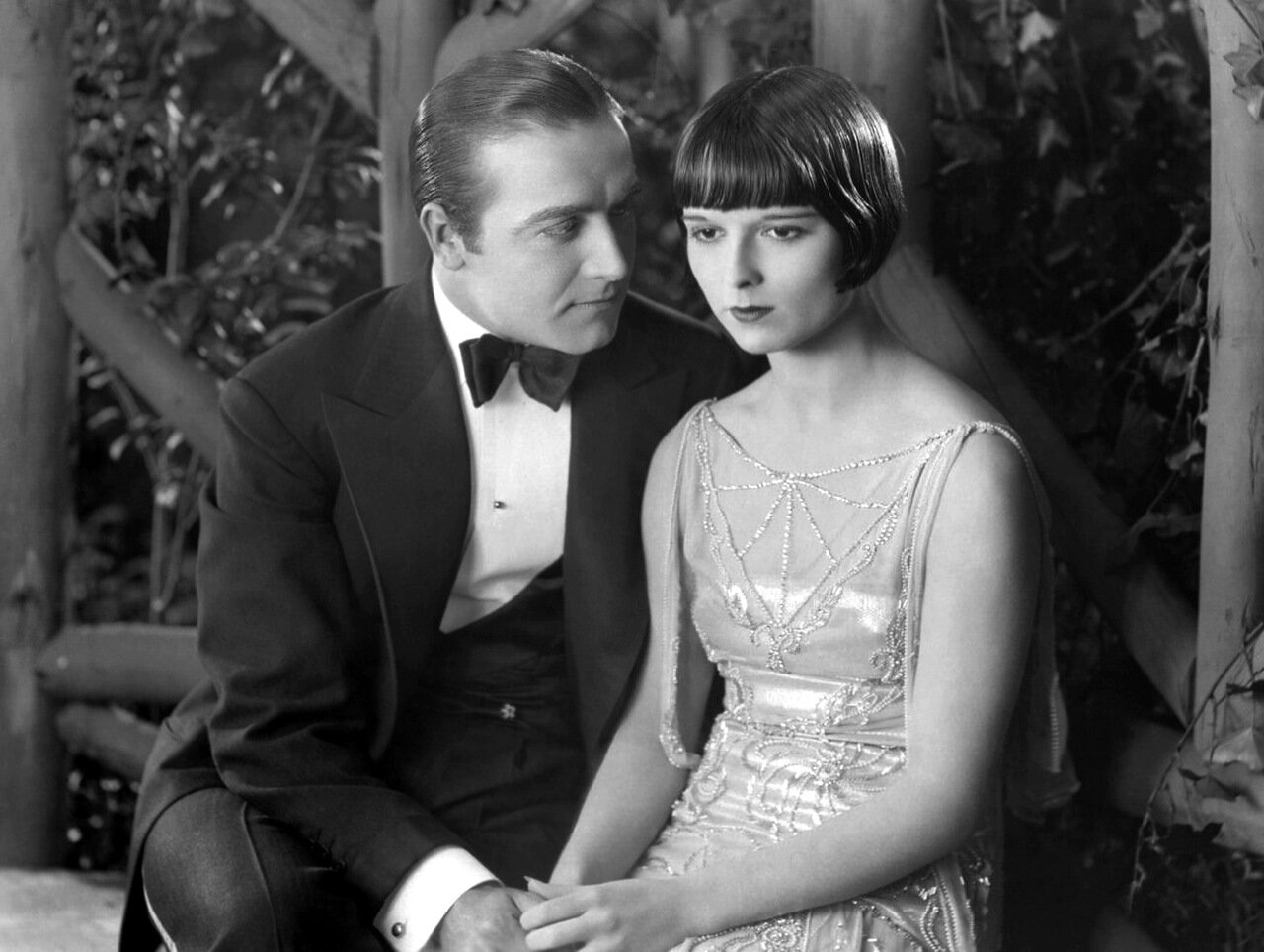 circa 1925: American actress Louise Brooks (1906-1985) shares a romantic arbour with a man in a scene from an unknown film.
