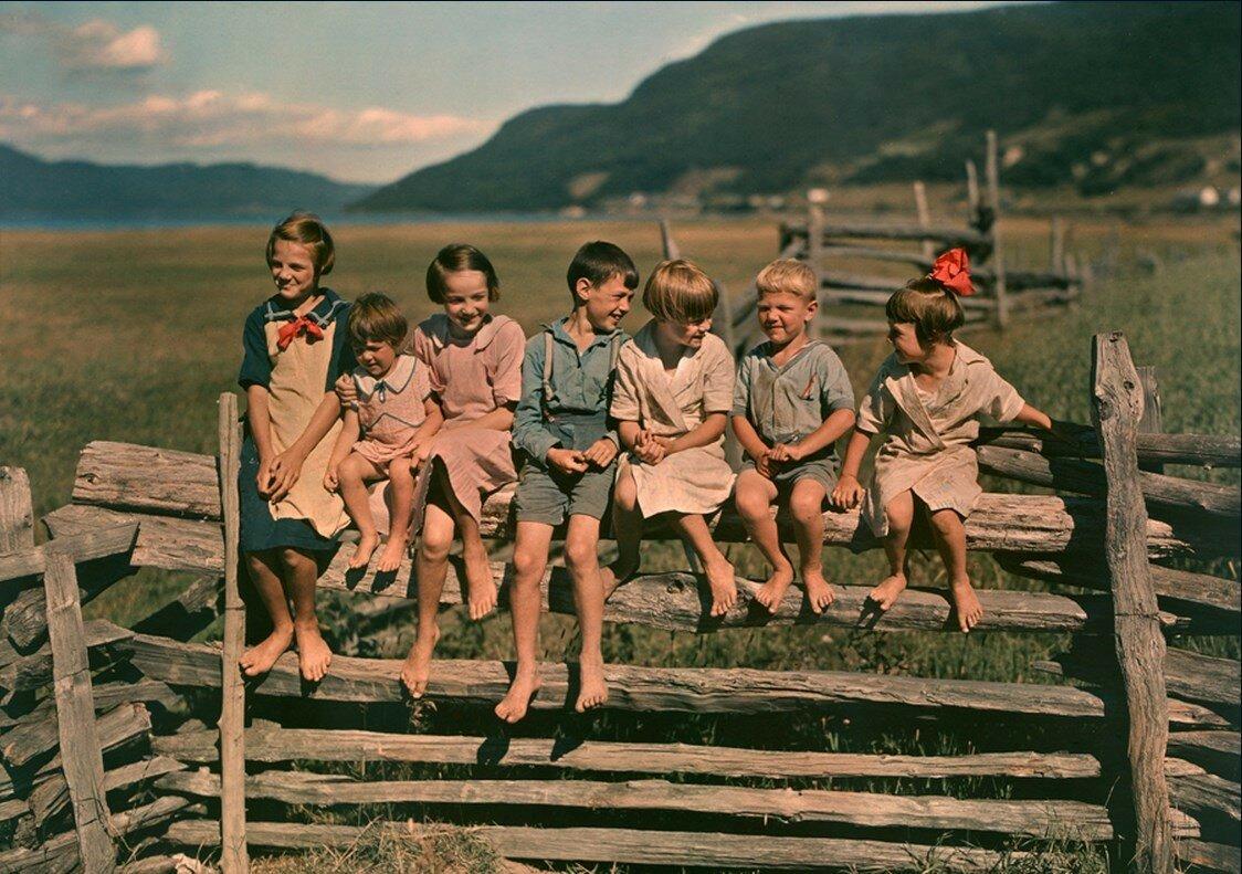 1939. Семь братьев и сестер, сидящих на деревянном заборе в Квебеке