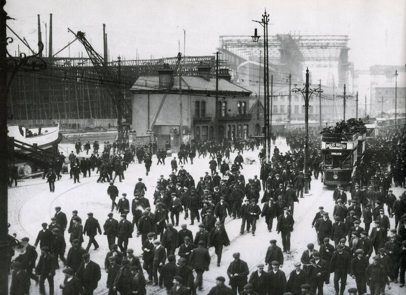 Workers leaving Harland & Wolff Shipyard, with RMS Titanic in the background. Belfast, 1911.