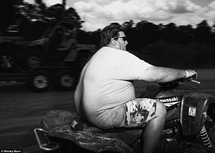 Мужчина в солнечных очках рассекает на квадроцикле Kawaski по «Яхт-клубу реднеков» во Флориде.
