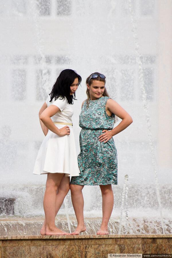 Девушки позируют на фоне фонтана