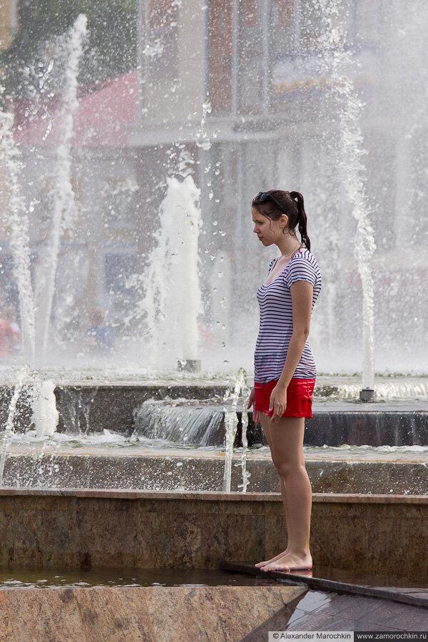 Девочка в одежде купается в фонтане