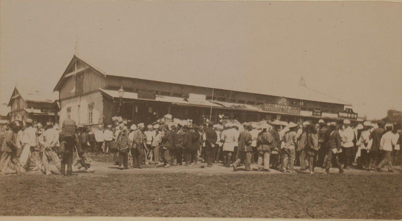 Толпы людей на рыночной площади в центре города. 1899