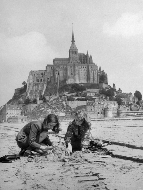 American travelers building a sand replica of France's medieval abbey at Mont-Saint-Michel in the background, July 1948.