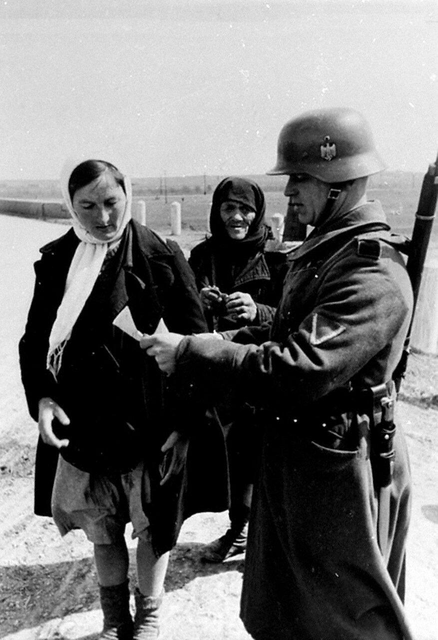 1942. Россия, ефрейтор проверяет документы у крестьянок