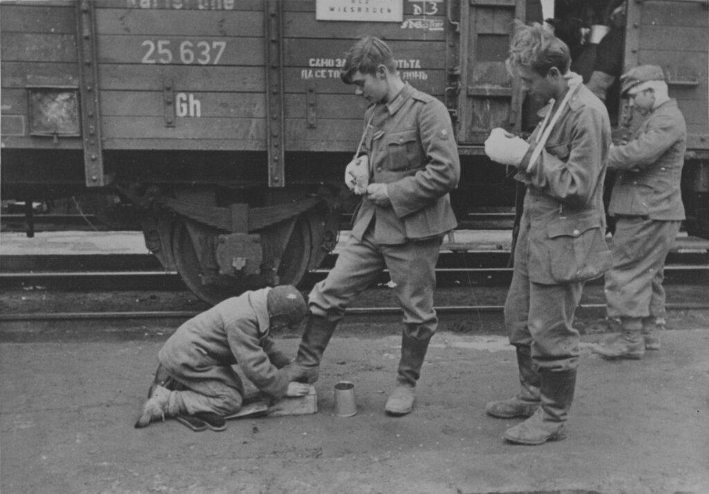 Подросток чистит сапоги раненому немецкому солдату на оккупированной железнодорожной станции в СССР. 1943 г.