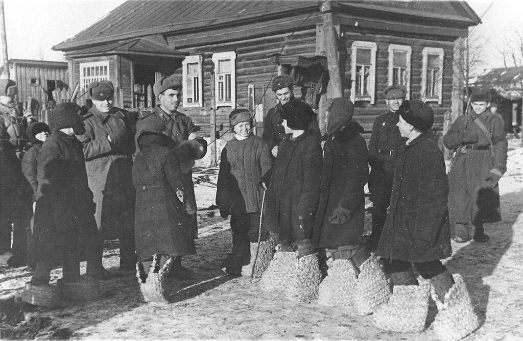 Школьники освобожденного Гжатска (Ныне — город Гагарин) показывают красноармейцам немецкие «эрзац-валенки». Смоленская область. Март 1943 г.