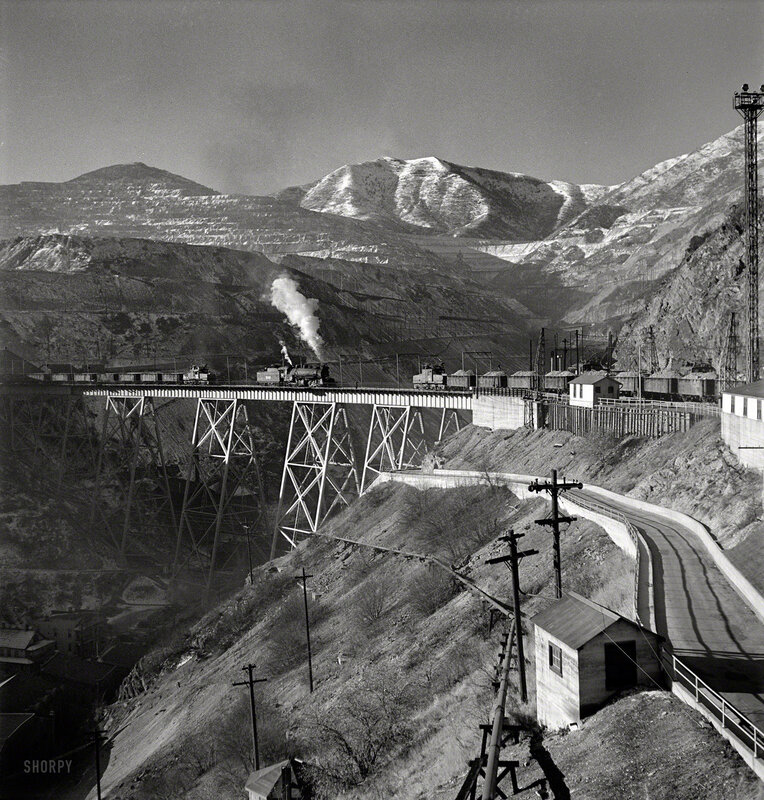 November 1942. Bingham Canyon, Utah. Ore trains on a trestle bridge above an open-pit mine of the Utah Copper Compan
