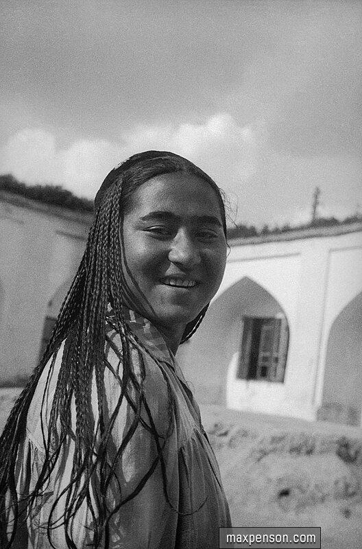 Девушка узбечка в национальном платье на фоне внутреннего дворика медресе