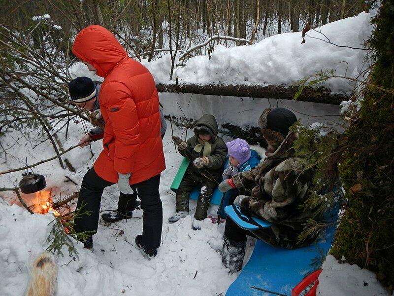 Пикник в снежном лесу на заячьей поляне у поваленной ели, чайник греется на костре