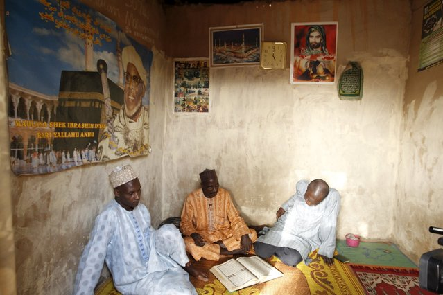 Shi'ite men talk while sitting under posters of their Islamic leaders in Zaria, Kaduna state, N