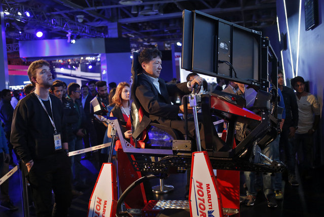 A visitor tries out Maruti Suzuki's Drive Simulator at the Indian Auto Expo in Greater Noida, o