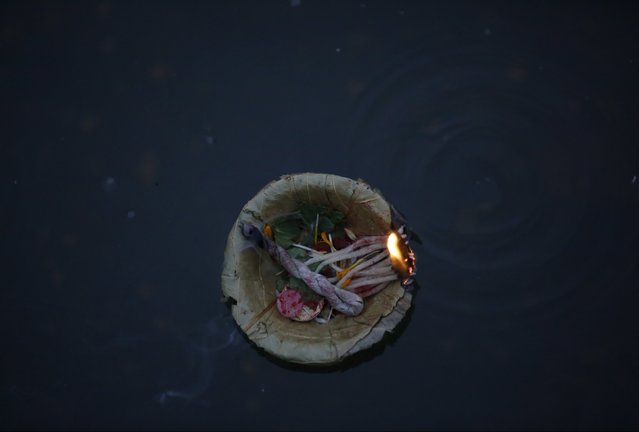 An offering floats on the Bagmati River during the Swasthani Brata Katha festival at Pashupatinath T