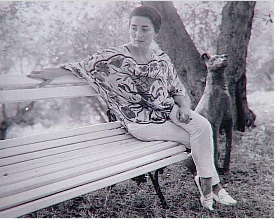 1966. Жаклин сидит на скамейке