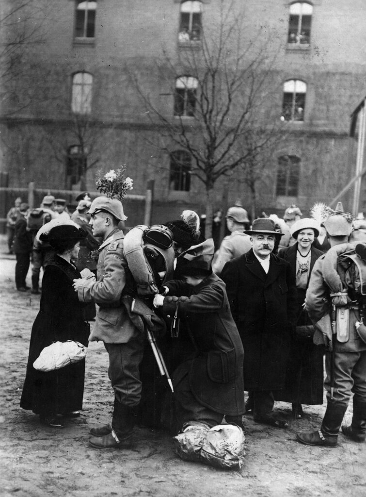 A German soldier with flowers on his helmet is helped by relatives with his equipment before shipping off to the war, c. 1914
