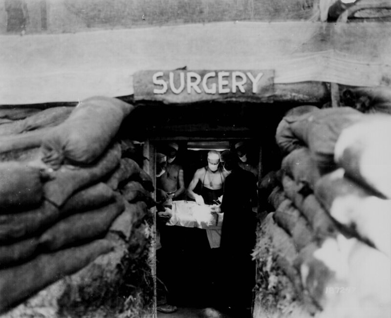 An American Army doctor operates on a U.S. soldier wounded by a Japanese sniper in an underground surgery room behind the front lines on Bougainville, December 13, 1943