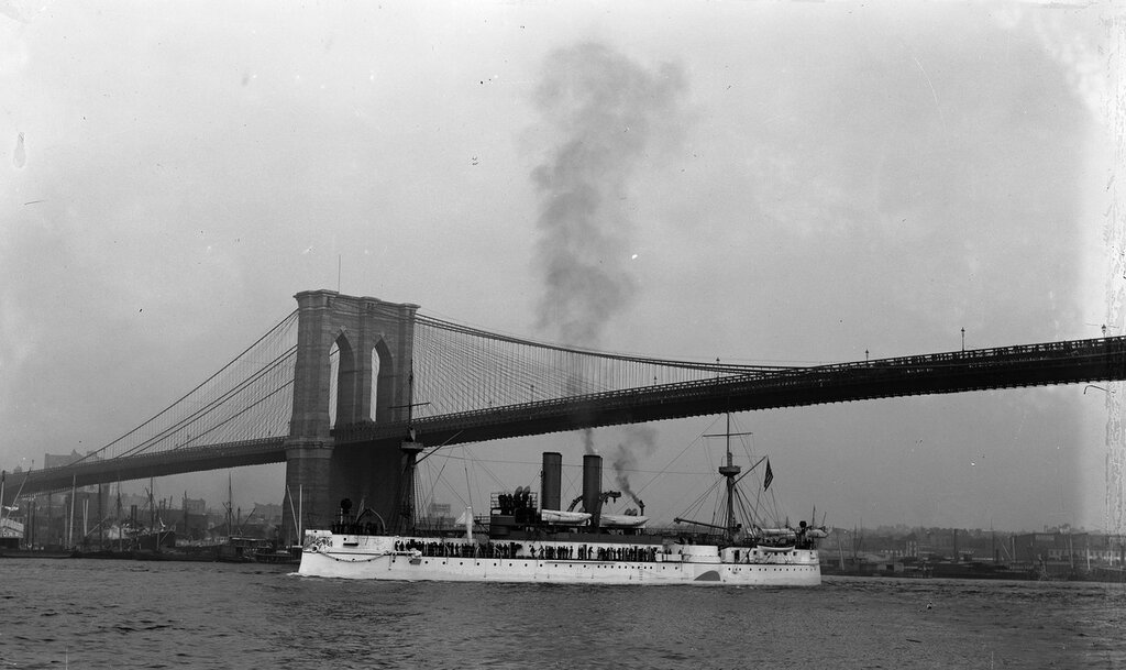 USS Maine, port view, passing under Brooklyn Bridge. 1895-98