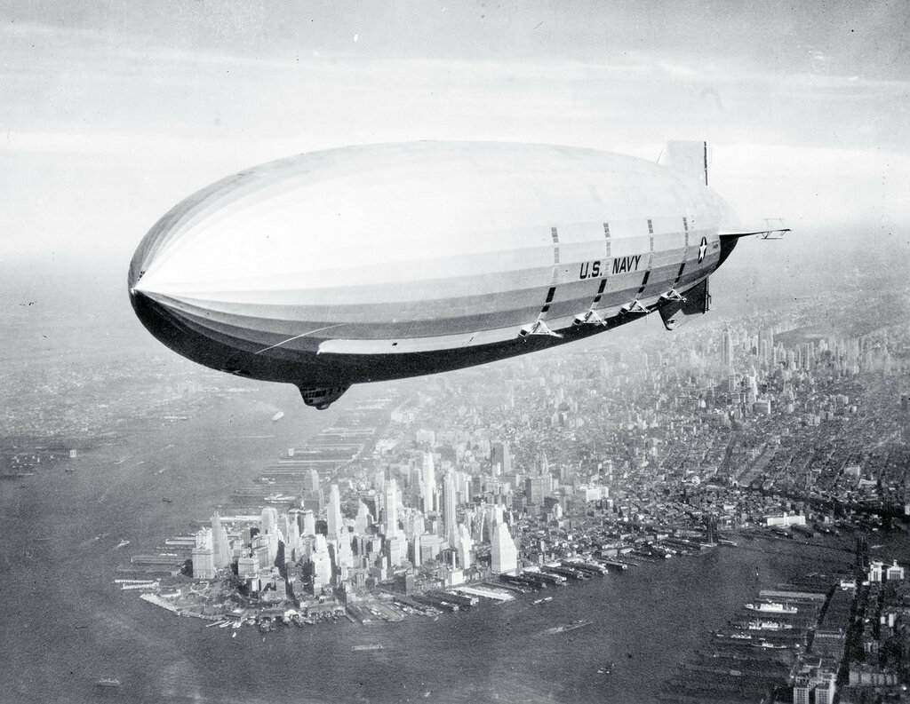 USS Macon (ZRS-5). Flying over New York Harbor, circa Summer 1933. The southern end of Manhattan Island is visible in the lower left center