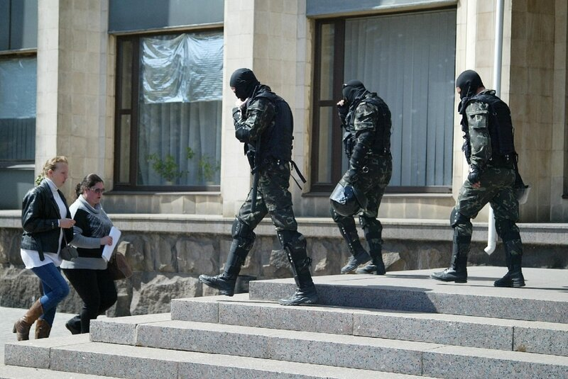 Women enter and gunmen leave a city administration building in the city of Donetsk, Eastern Ukraine, Wednesday, April 16, 2014. Kiev authorities and Western countries say tens of thousands of Russian troops are stationed near the border with Ukraine and f
