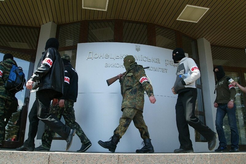 Men in uniform, one of them with a gun on a shoulder, wearing hand bandages of so-called Slavic patriotic organization reading: Oplot ( Stronghold), enter a city administration building in the city of Donetsk, Eastern Ukraine, Wednesday, April 16, 2014. K