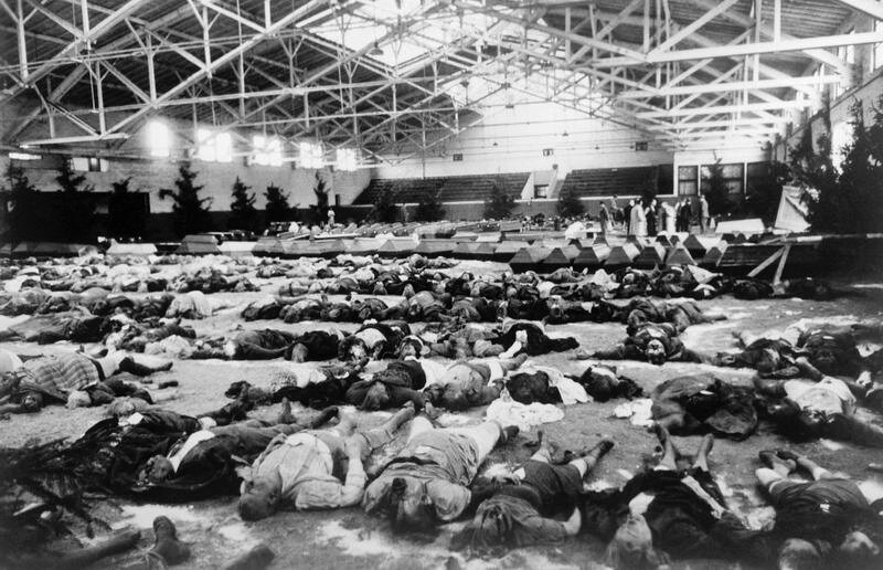 Berlin, December 1943: victims of a bombing raid are laid out for identification and burial in a gymnasium decorated with Christmas treesHU 12143