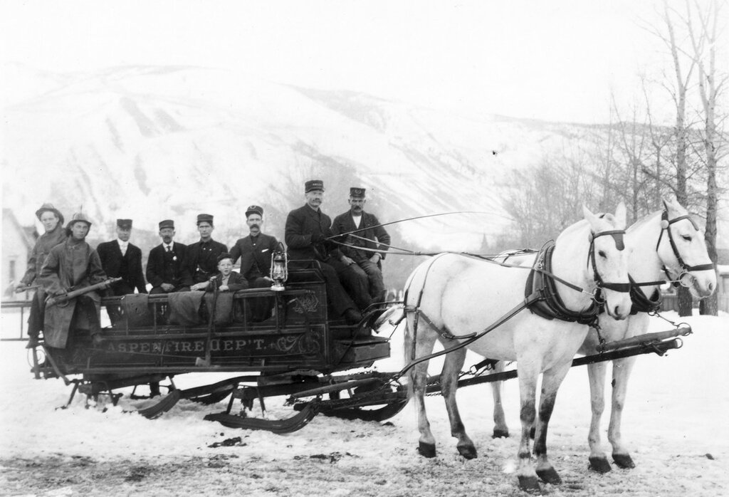 The firemen of the Aspen, Colorado, Fire Department sit in a sledge drawn by two horses. 1886
