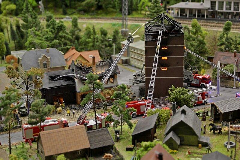 Гранд макет: пожарные машины с лестницами и пожарные из брадспойтов тушат горящее здание