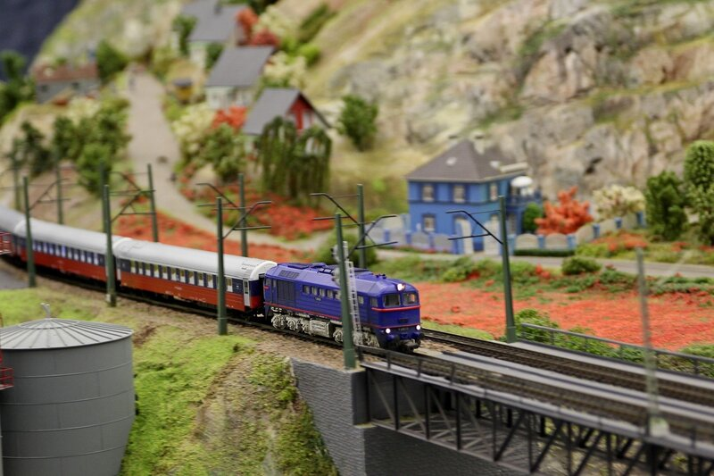 Гранд макет: электричка въезжает на железнодорожный мост в горной местности