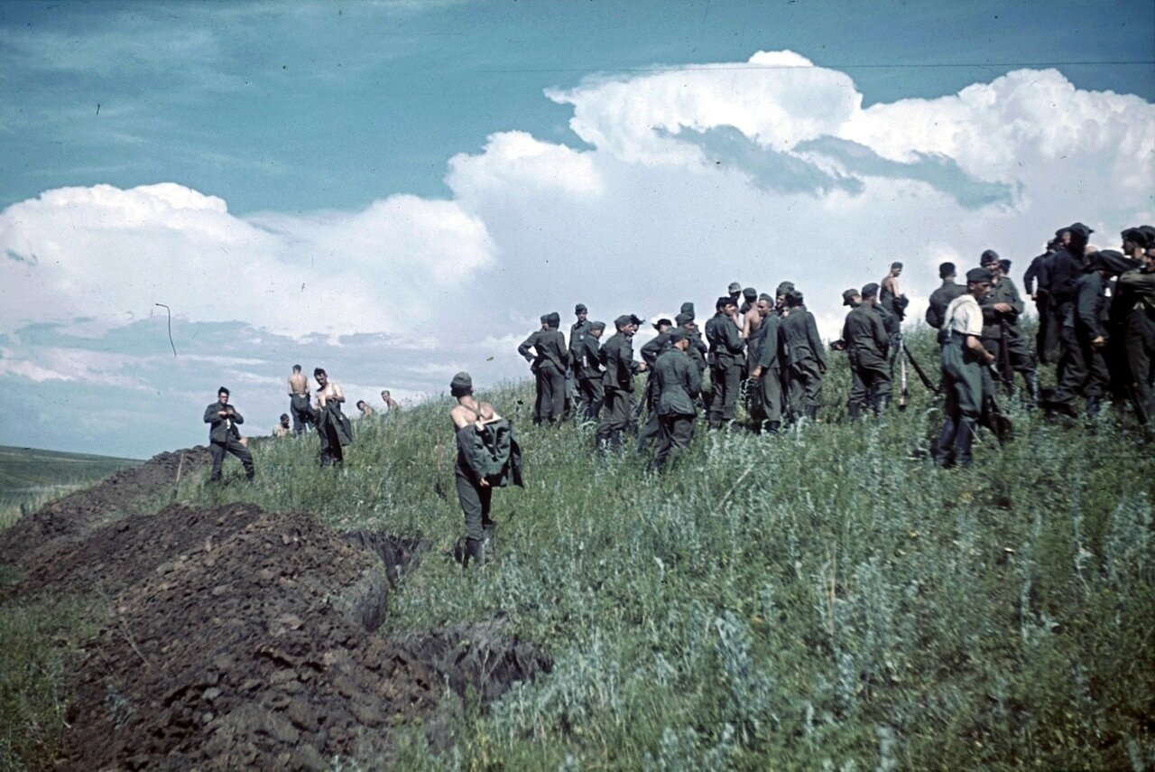 Группа немецких солдат у вырытых окопов на склоне холма в Белгородской области.