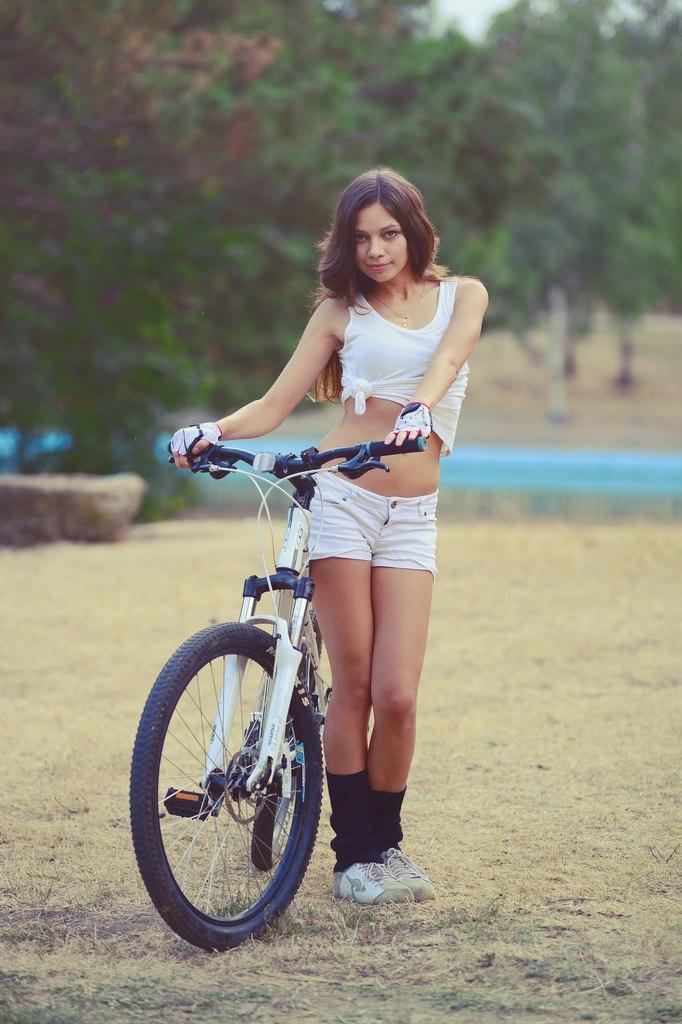 Заводящая красотка с велосипедом в белом топике