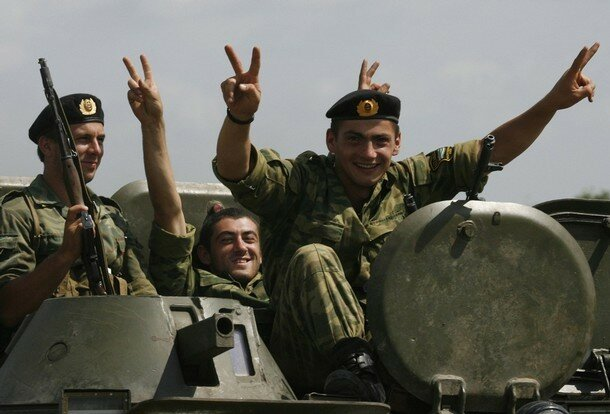 Abkhazian rebel fighters wave as they return from their separatist region's border with Georgia proper near town of Gali